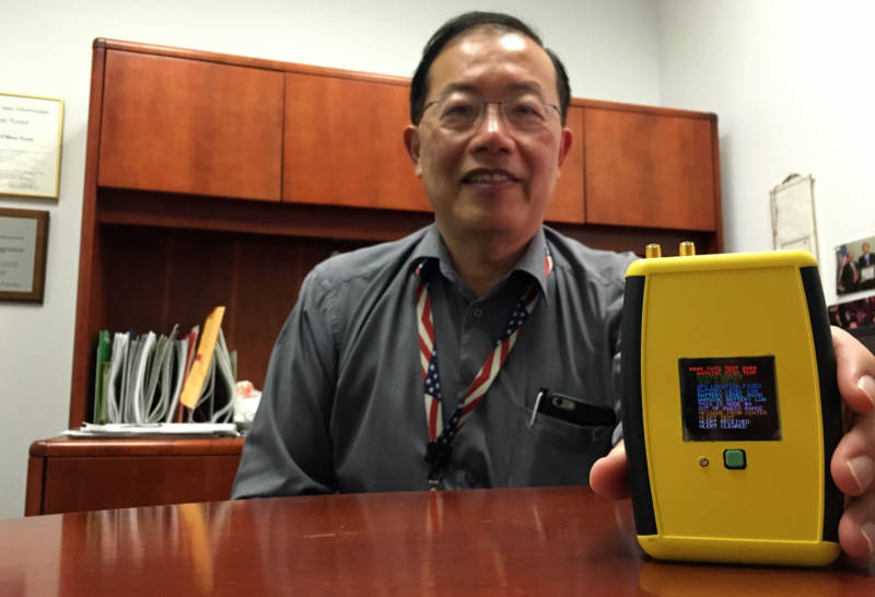 Ed Chow with NASA's Jet Propulsion Laboratory shows off the Personal Alert and Tracking System he helped develop for firefighters.