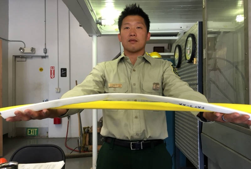 Sam Wu holds out two samples of fire hose used at the San Dimas Technology and Development Center.