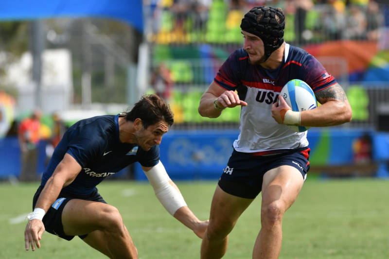 USA's Garrett Bender (R) runs with the ball in the men's rugby sevens match against Argentina during the Rio 2016 Olympic Games on Tuesday.