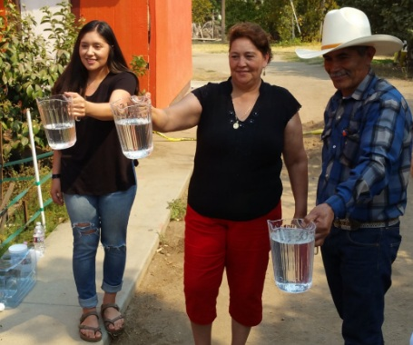 East Poterville residents display water delivered by a new system connecting the unincorporated town.