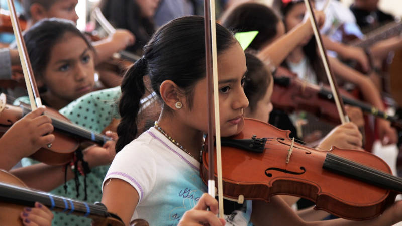 Yuritzi Guerrero practices violin with several other campers.