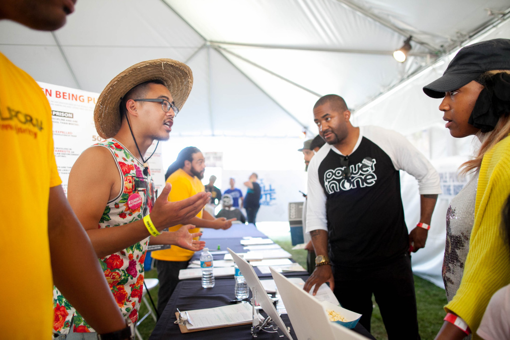 Matthew Vu (L), talks to local residents about issues that will be on the ballot during a music and art festival in Martin Luther King Jr. Park in South Los Angeles on Saturday, Sept. 3, 2016.