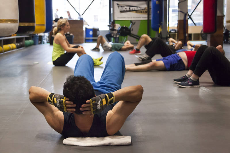 Fighters in the Rock Steady boxing class lay on the floor before starting their abdominal exercises at the end of the workout.