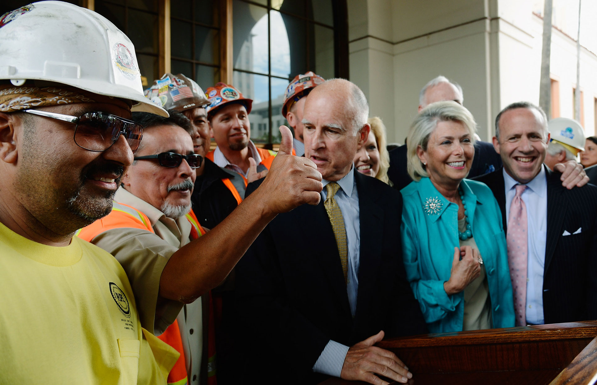 Gov. Jerry Brown is surrounded by construction workers and elected officials after signing legislation authorizing initial construction of the high-speed rail line at Union Station on July 18, 2012 in Los Angeles.