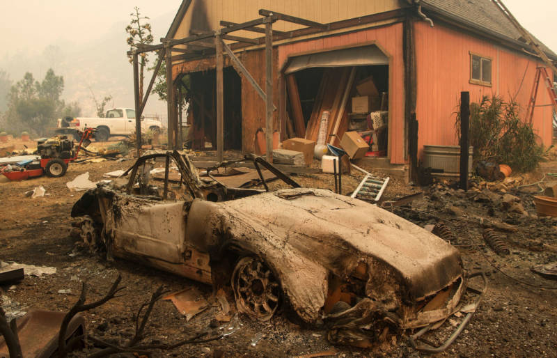 A burned out Porsche sits near a home partially burned by the Loma Fire in the Santa Cruz Mountains on September 27, 2016.