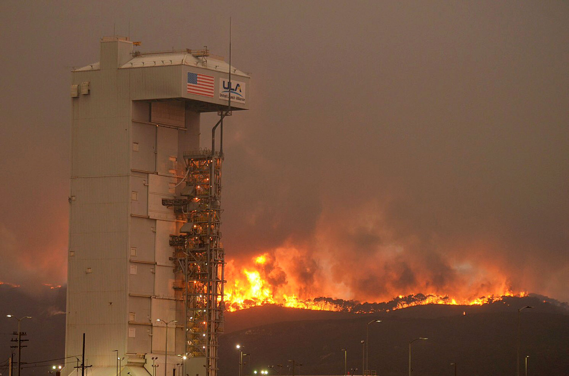 The Canyon Fire burns on Vandenberg Air Force Base. In the foreground is Space Launch Complex-3 housing the Atlas V rocket and WorldView 4 satellite.