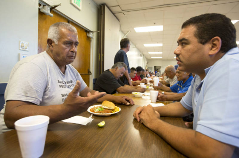 Rigoberto Bejarano (L) talks with intake coordinator Salvador Mendoza at Proyecto Pastoral. The group established The Guadalupe Homeless Project in 1988.