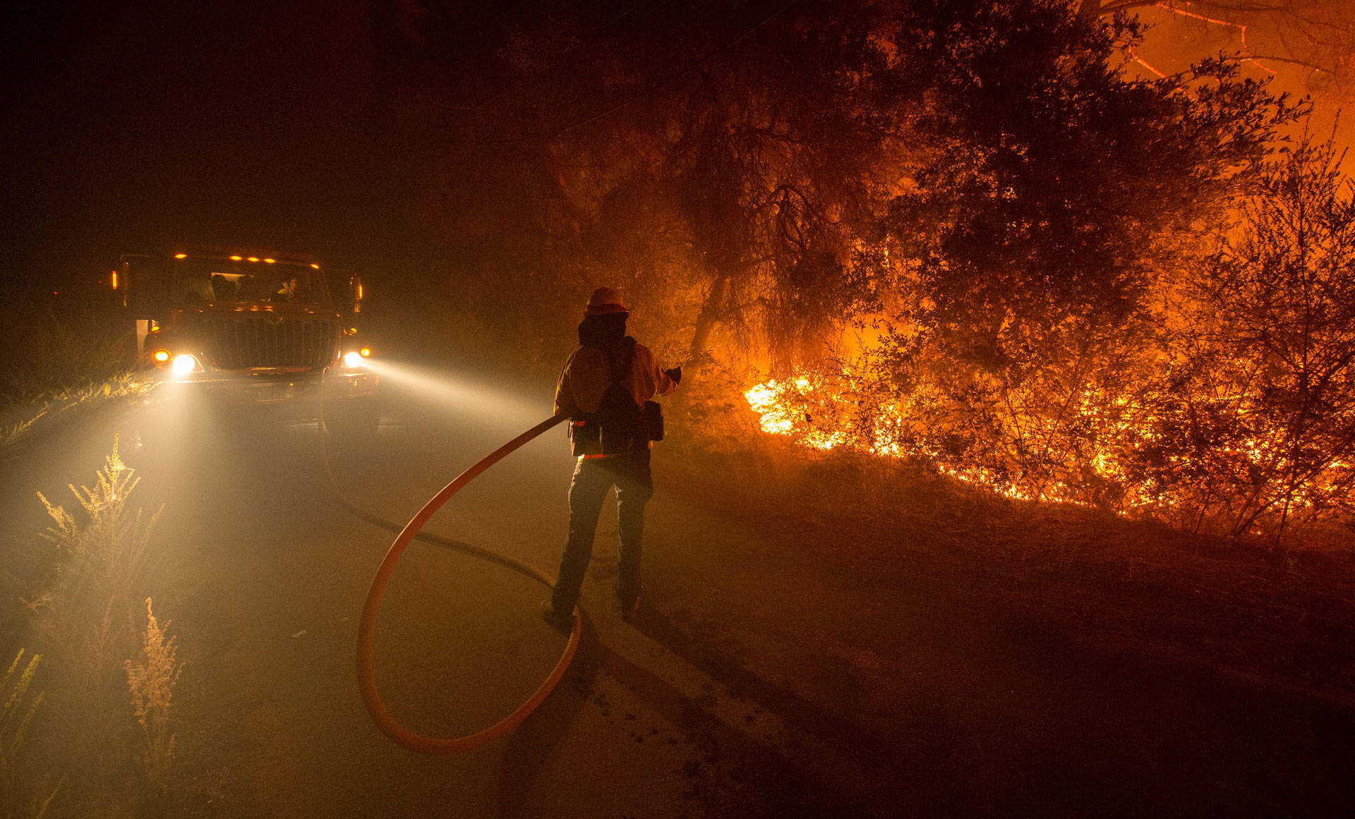 A firefighter douses flames as they approach a road in the Santa Cruz Mountains near Loma Prieta on Sept. 28, 2016. Josh Edelson/AFP/Getty Images