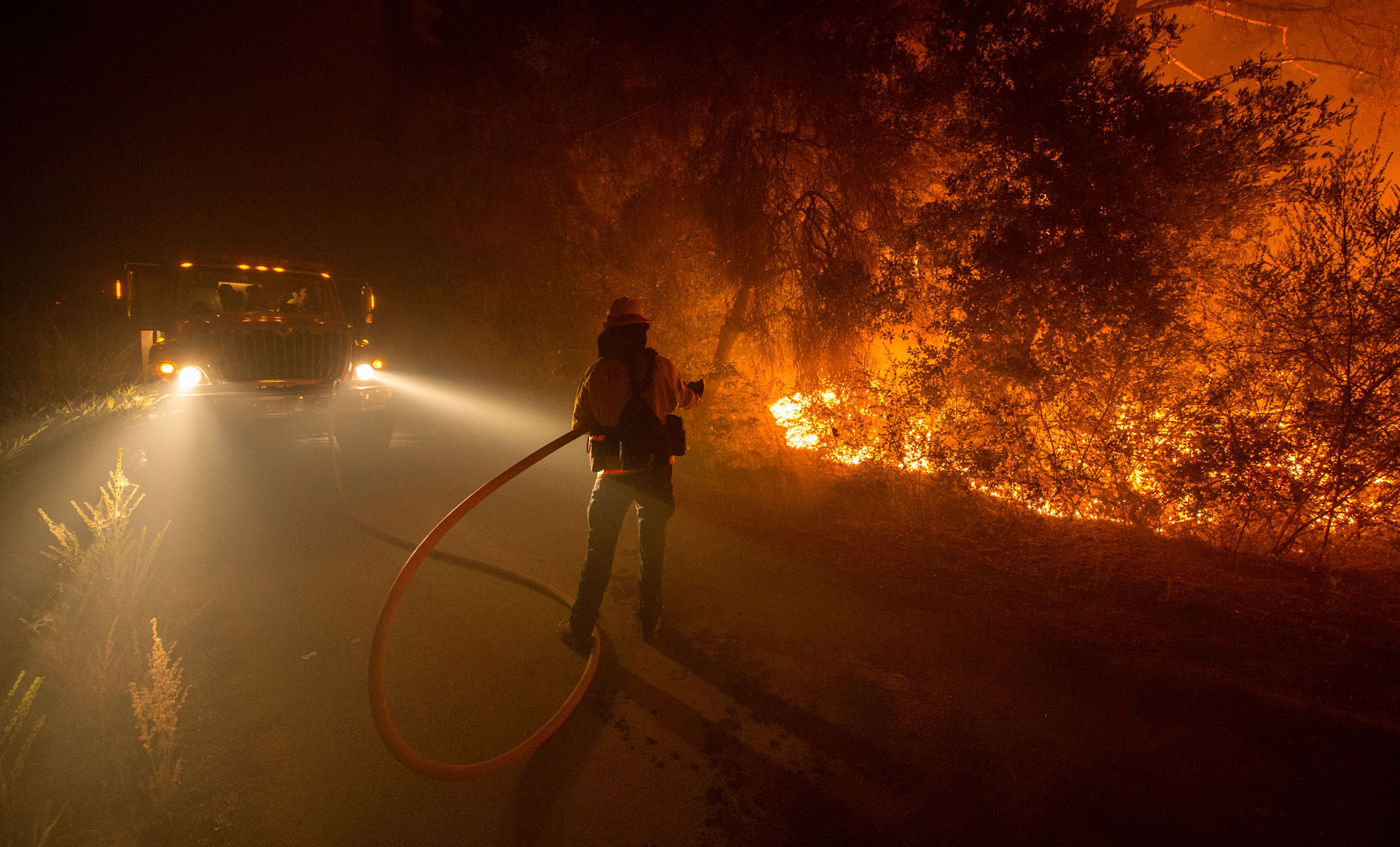 A firefighter douses flames as they approach a road in the Santa Cruz Mountains near Loma Prieta on September 28, 2016.