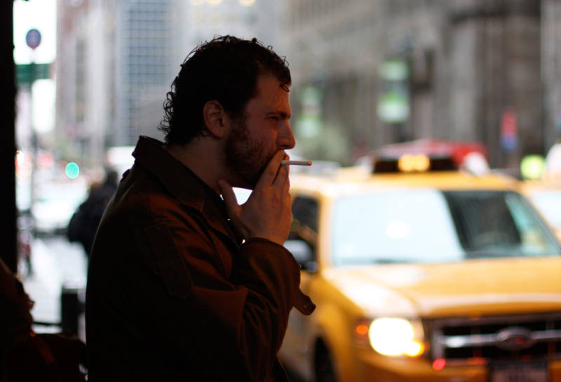 A man smokes a cigarette in New York City, where the current tobacco tax is $4.35 a pack.