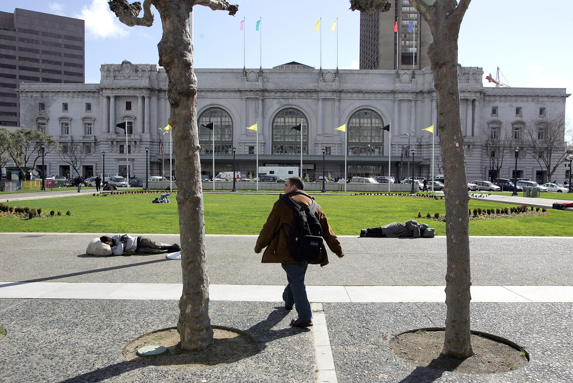 A man walks by two homeless people sleeping outside in the San Francisco Civic Center.
