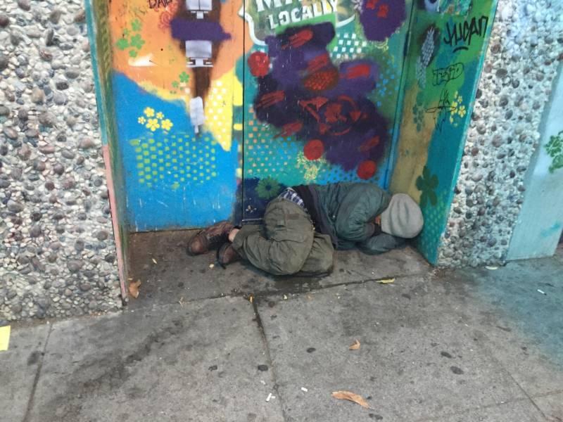 A homeless man sleeping in a doorway in San Francisco.