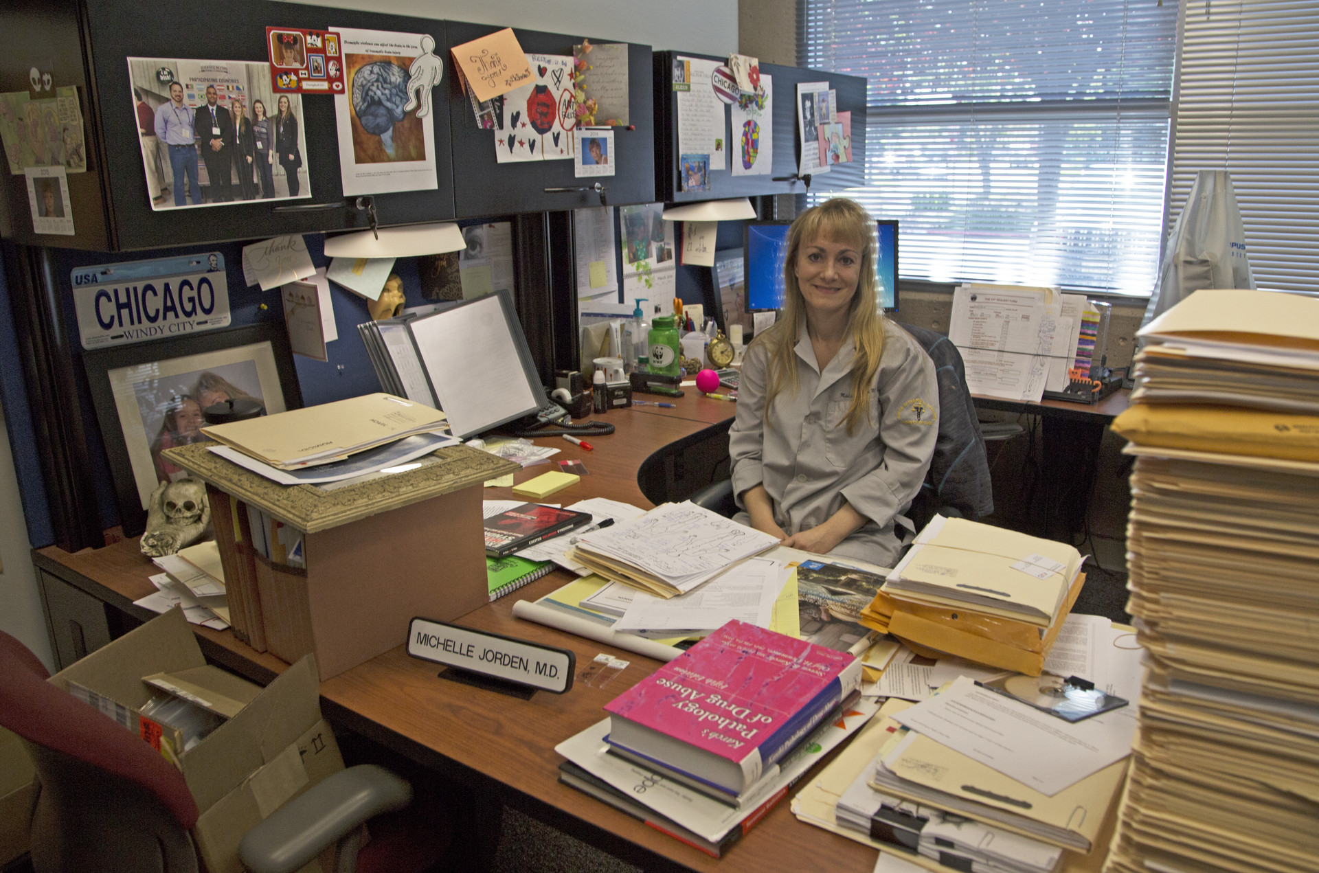 Completed and reports for review are stacked high on the desk of Assistant Medical Examiner Michelle Jorden.