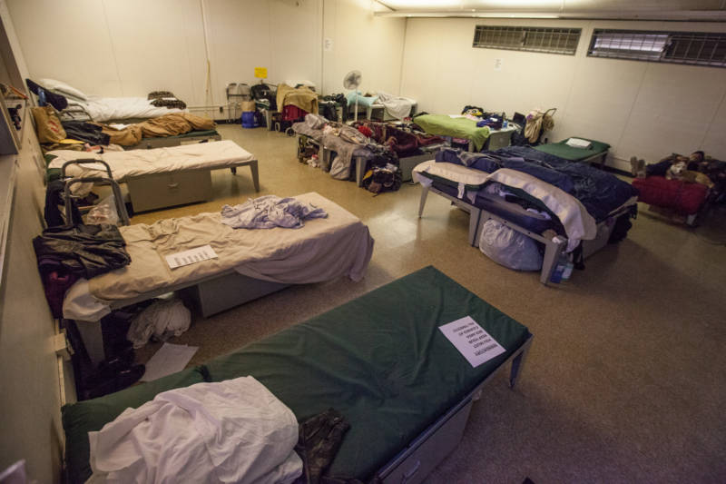 A couple people sleep in a dormitory at a Navigation Center in San Francisco. Unlike other centers, couples are allowed to push their beds together here, and dogs sleep with their people.