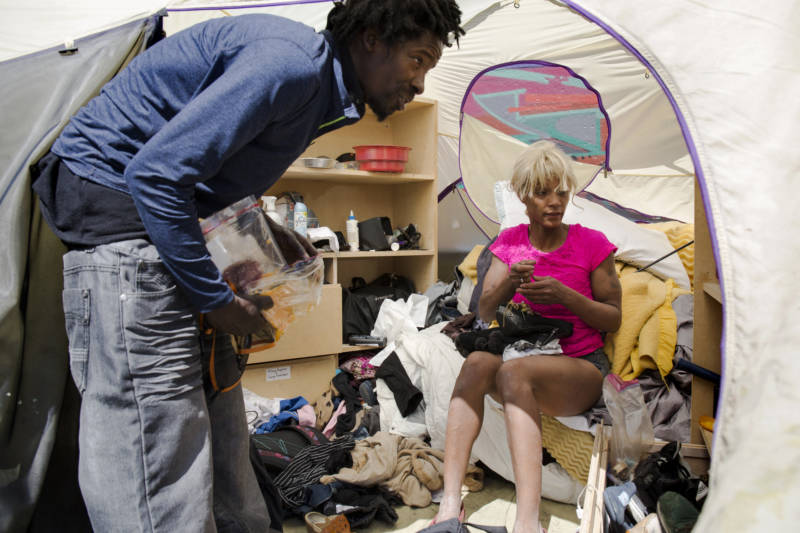Chase and Monique talk in their tent on Florida St. that is part of a homeless encampment in the Mission District of San Francisco.