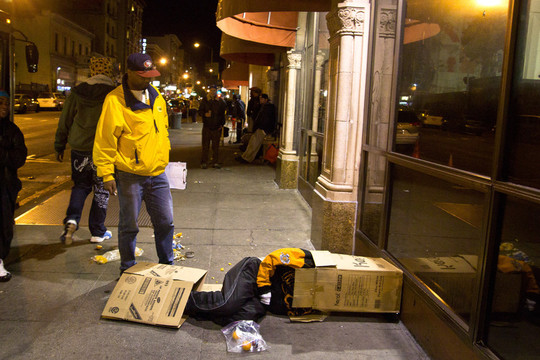 A homeless man waiting in line outside of Glide uses a box for warmth and tries to get some sleep.