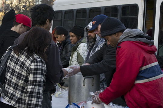Volunteers with a church group serve free meals to people at U.N. Plaza in San Francisco.