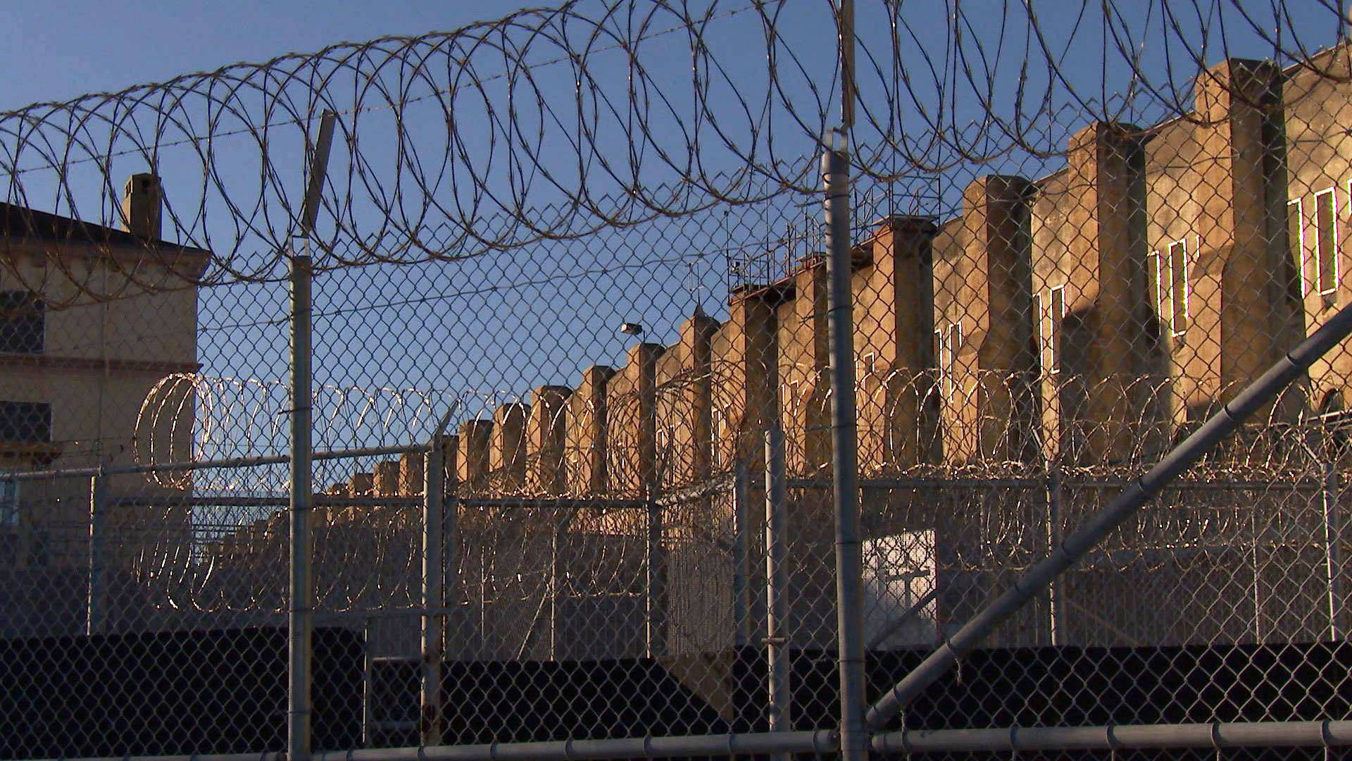 Barbed wire and fences separate death row inmates from the rest of the population at San Quentin.  KQED