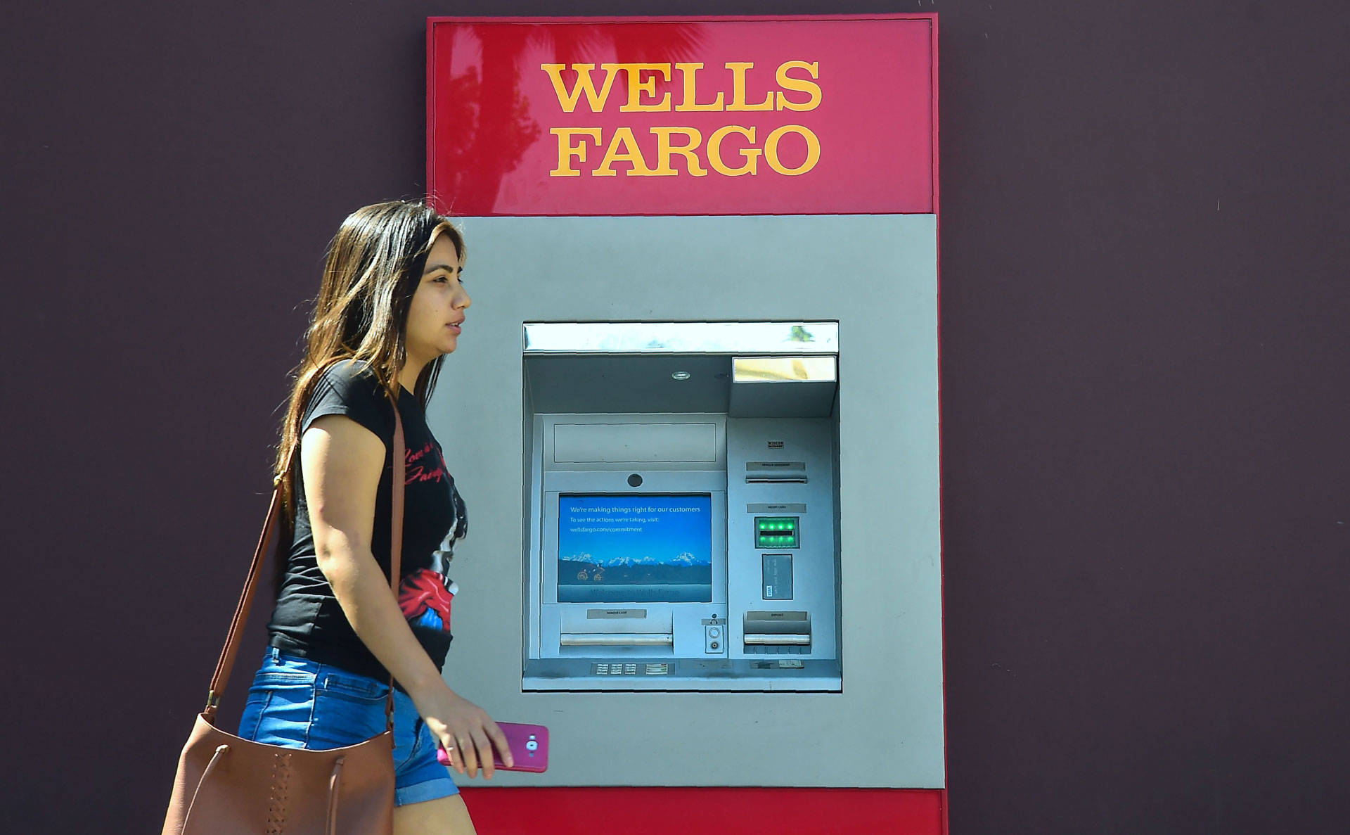 A woman walks past a Wells Fargo ATM in Pasadena on September 28, 2016. California Treasurer John Chiang said the state will suspend several banking relationships with Wells Fargo to sanction the firm following allegations of 'fleecing its customers.'