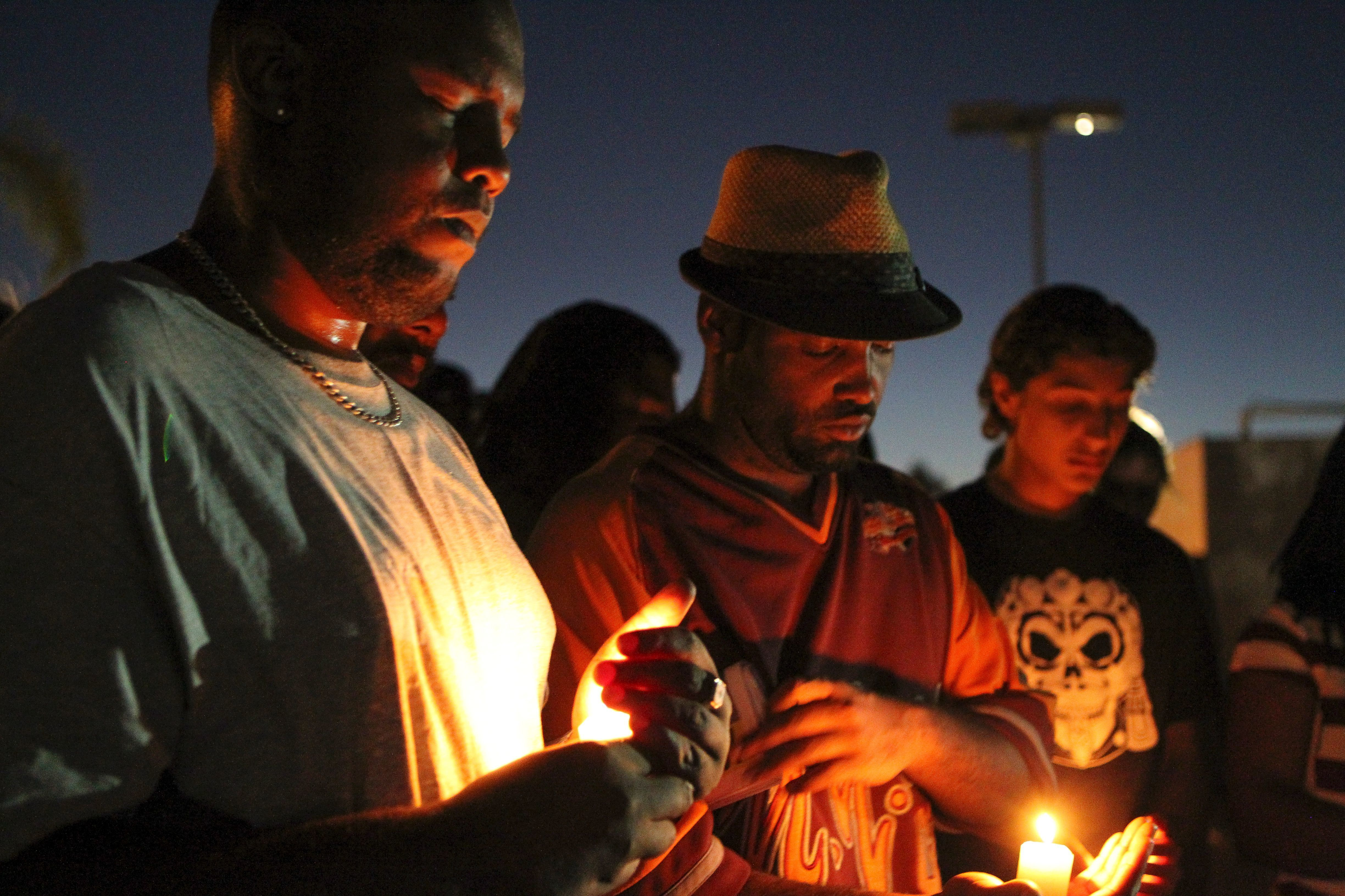 Mourners and activists hold a candlelight vigil during a rally in El Cajon, a suburb of San Diego, Calif., on Wednesday, in protest of the police shooting the day before.