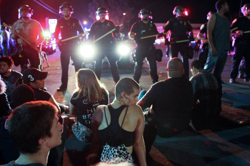 Protesters sit in front of a police line in El Cajon, a suburb of San Diego, Calif., on Wednesday night.