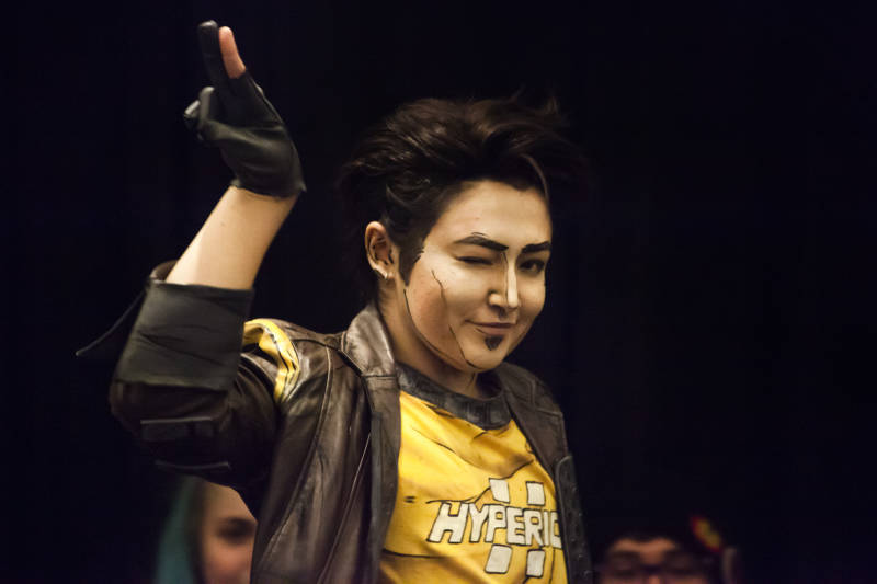 Cosplay character Handsome Jack, from the video game Borderlands: The Presequel, winks and waves on stage during the GX 4 Cosplay Pageant