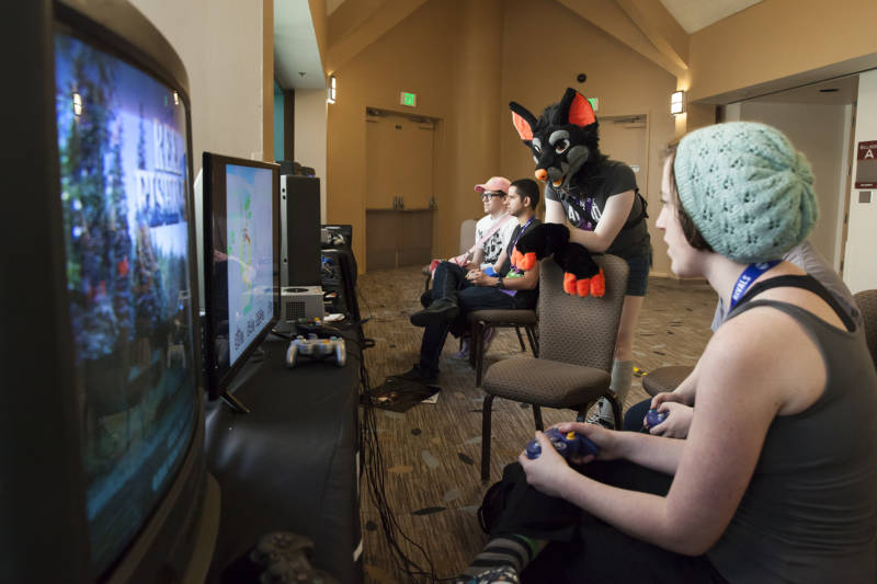 Sam (center) watches as two of her friends play video games in the Magfest Arcade.
