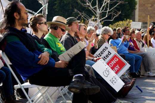 Several people listen to a speaker express her opposition to the Citizens United ruling at an Occupy Courts protest in Los Angeles in 2012.