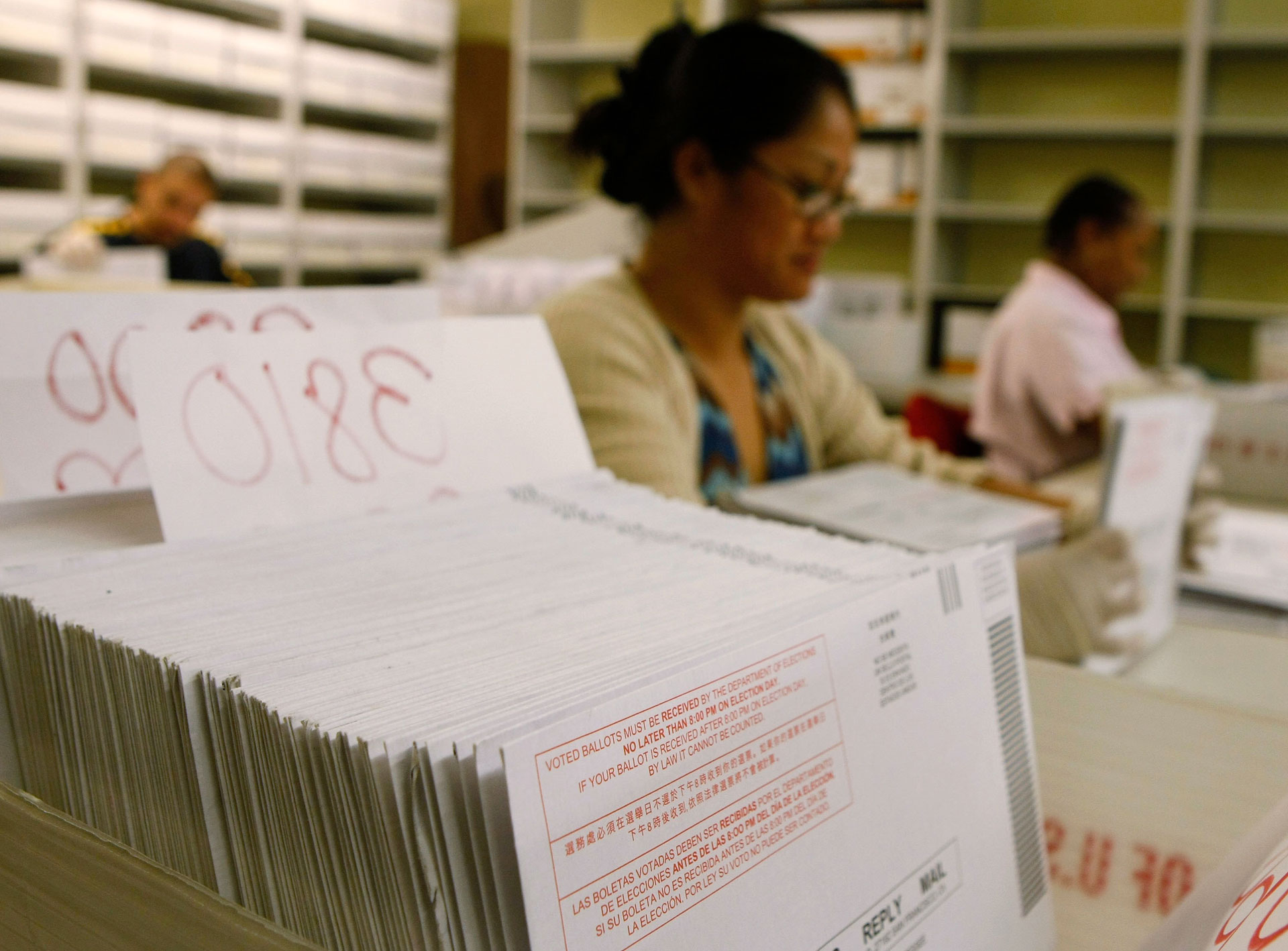 San Francisco election workers sort stacks of vote-by-mail ballots.