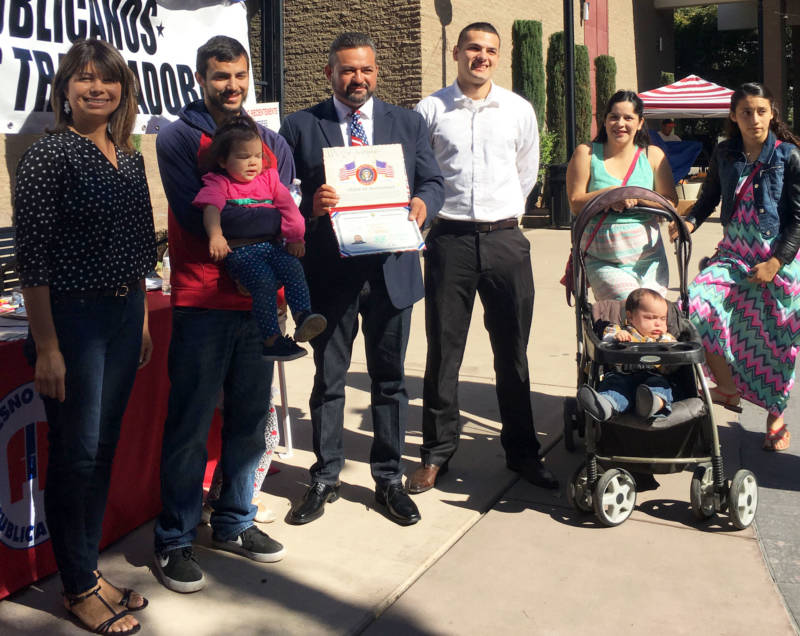 Israel Cervantes (C, with certificate), a Donald Trump supporter, stands with his family after his naturalization ceremony.