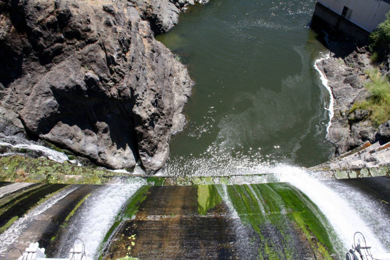 Water spills down the mossy face of the Copco 1 Dam, on the Klamath River outside Hornbrook.