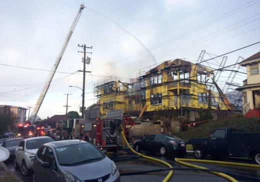 A four-alarm fire gutted an apartment complex under construction near Oakland's Lake Merritt Monday morning.