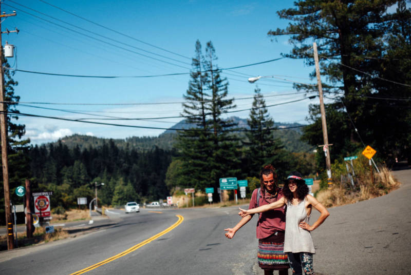 """Khaled Mourra (L) of Mexico and Mayssan Charafeddine of Montreal try to hitch a ride in Garberville, Calif. During harvest season, """"trimmigrants"""" crowd the town's sidewalks jockeying for jobs with homemade signs or try to meet potential employers by frequenting local bars."""