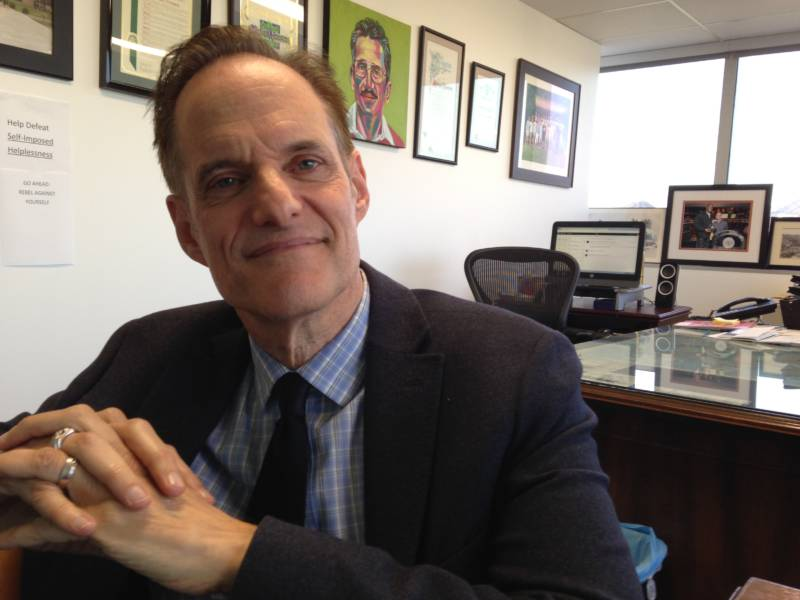 Michael Weinstein, president of the AIDS Healthcare Foundation, in his office in Los Angeles. Behind him is a painting of Chris Brownlie, who worked with Weinstein to found the first AIDS hospice in LA.