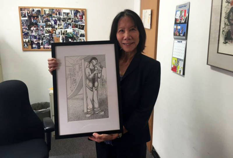 Patricia Lee, managing attorney of the San Francisco Public Defender's Juvenile Division, holds artwork that she feels demonstrates the challenges many of her clients face.