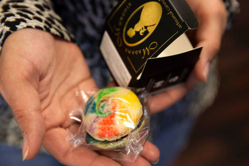 A staff member at a dispensary in San Francisco holds a cannabis-infused macaroon.