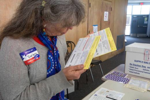 Poll worker Darlene Farnes examines some mail-in ballots at a polling station at a high school June 7, 2016 in San Diego, California.