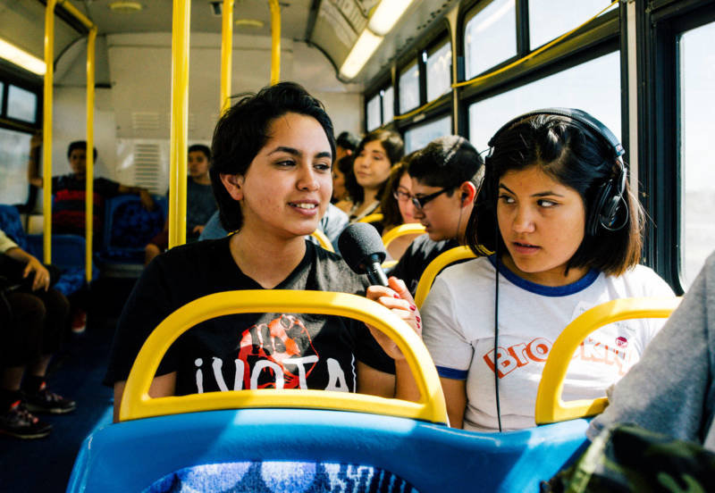 Rosy Mendez (L) rides a slow-moving bus through the Eastern Coachella valley to get to the library to get her homework done.