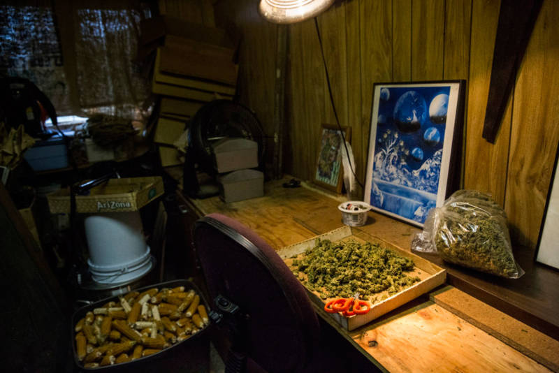 Terri sat in an office chair in this cramped shack, trimming marijuana buds. She and three other trimmers were paid $200 for every pound. They wore aprons and tracked their work with paper and pencil.