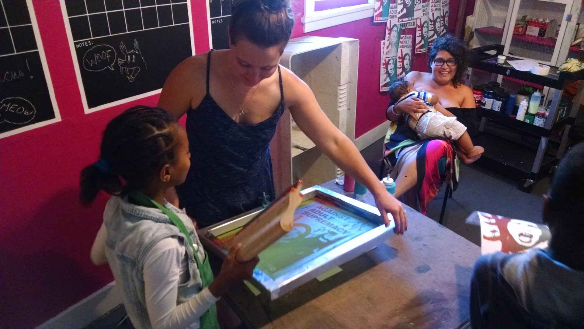 Franki Velez (with baby) helps teach screenprinting at the Omni Commons.