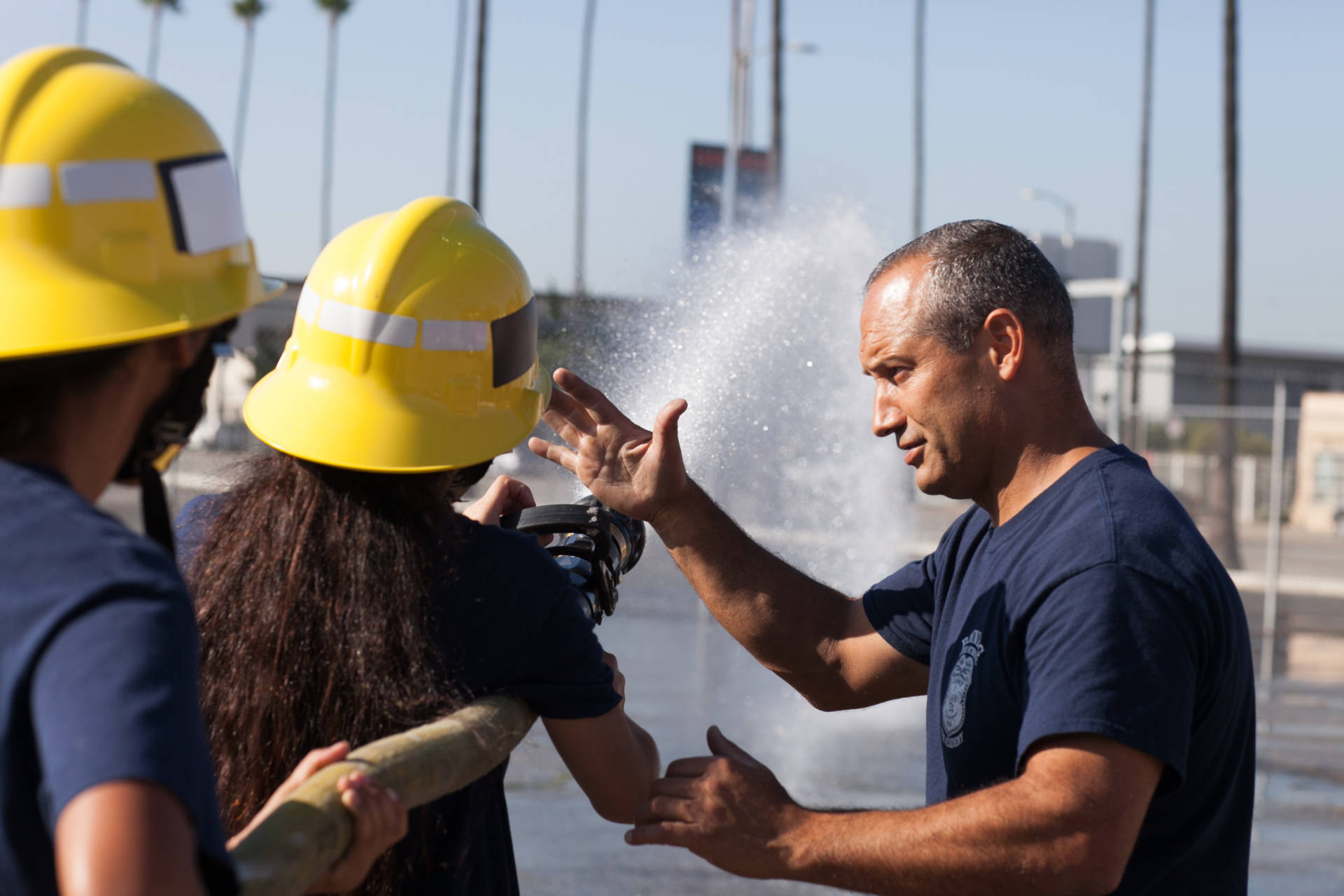 LAFD Capt. Eddie Marez instructs cadets at Banning High on how to operate a fire hose. Roxanne Turpen/NPR