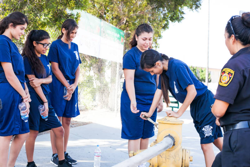Gail Sonoda (R), an instructor and firefighter with the Los Angeles Fire Department, teaches young cadets how to work a hydrant.