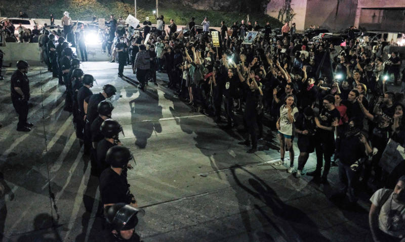 Protesters (R) confront a line of police as they shut down the 101 Freeway in Los Angeles Wednesday night.