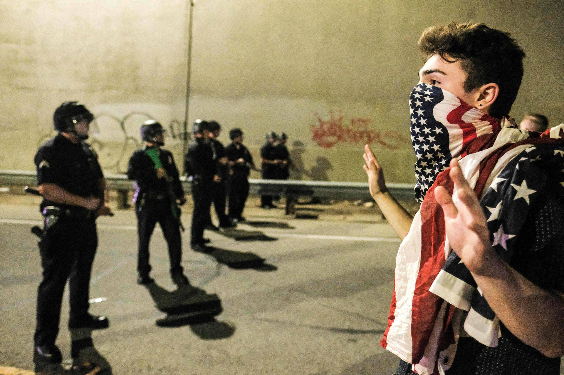 A protester (R) confronts police as protesters shut down the 101 Freeway following a rally one day after Donald Trump's presidential election victory in Los Angeles, late on November 9, 2016.  RINGO CHIU/AFP/Getty Images