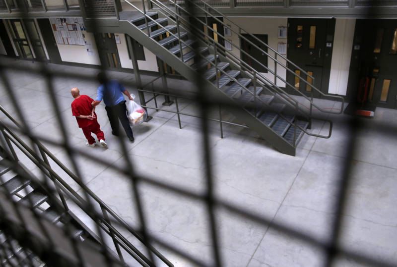 A guard escorts an immigrant detainee from his 'segregation cell' back into the general population at the Adelanto Detention Facility in Adelanto, California.