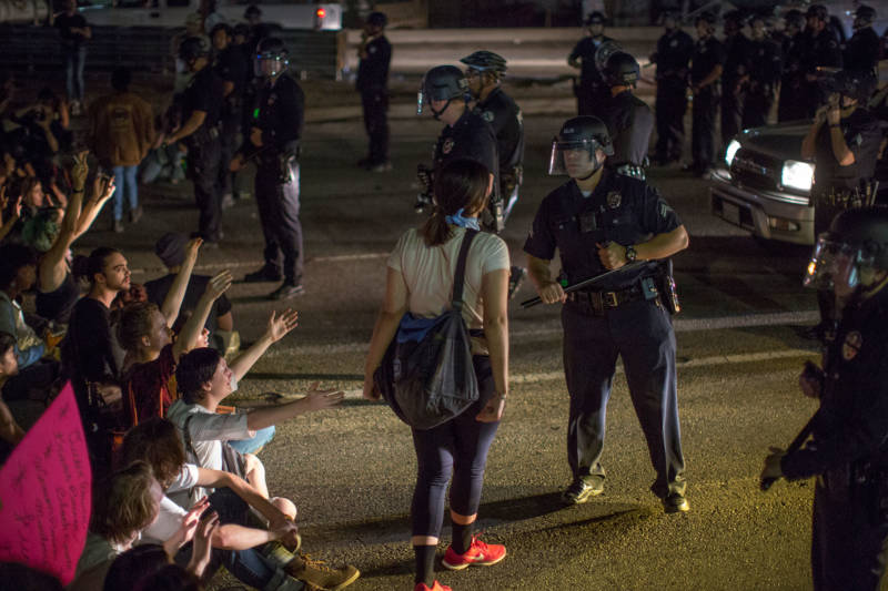 A woman yells at a police officer as protesters shut down the 101 Freeway in Los Angeles on Wednesday night.