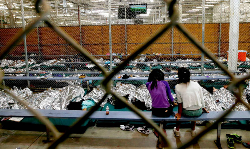 Two young girls watch television from their holding area where hundreds of mostly Central American immigrant children were being processed and held at the U.S. Customs and Border Protection Nogales Placement Center in June, 2014.