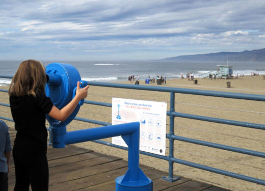 A child looks through one of the VR viewfinders on the Santa Monica pier.