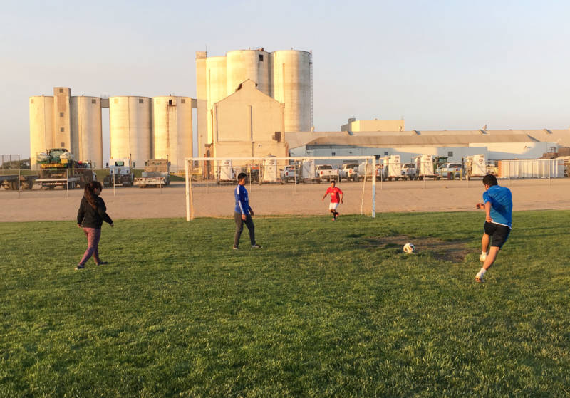 With remnants of the old sugar factory in the background, Tanimura and Antle employees play soccer after working in the fields.