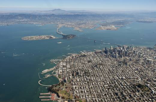 The Bay Bridge and the San Francisco Bay are seen from above.